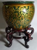 A 20th century ceramic jardiniere with gold foliate decoration on a hardwood stand,
