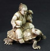 A Japanese ivory okimono of a man, Meiji period, carved seated on the back of a turtle,