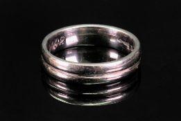 A platinum wedding ring, Millennium marks 2000, maker's mark RG, ring size T 1/2, 11.6g, inscribed.