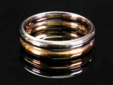An 18ct two colour gold wedding ring, by How, Sheffield assay, set with a single diamond,