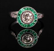 An emerald and diamond ring of circular cluster design,