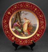 A Vienna style porcelain plate, circa 1900, painted with two classical figures in a landscape,