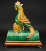 A Chinese pottery sancai glazed roof tile, in the form of a phoenix, mounted on a hardwood stand,