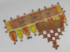 An Indian tent hanging, worked in coloured threads with a flowerhead panel, with fringe detailing,