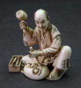 A Japanese ivory okimono of a craftsman, Meiji period,