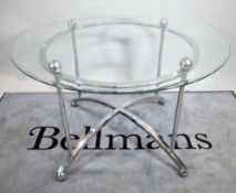 A 20th century glass circular dining table on chrome base, united by 'X' frame stretcher,