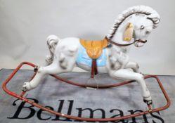 A 20th century fibre glass rocking horse on metal base, 125cm wide x 86cm high.