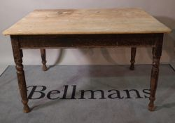 An early 20th century pine kitchen table on black painted turned supports, 120cm wide x 74cm high.