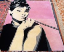 A machine made rug, the pink field depicting Audrey Hepburn, smoking a cigarette in a long holder,