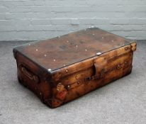 A coffee table with rectangular loose glass top on a brass studded polished leather suitcase,