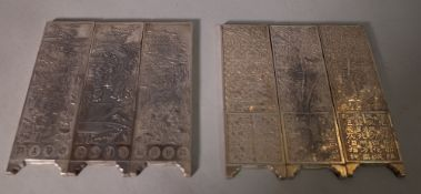 A set of three 20th century Chinese white metal scroll weights, framed as screen panels,