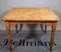 An early 20th century pine kitchen table on turned supports, 102cm wide x 74cm high.