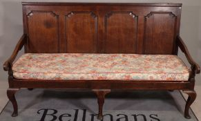 An 18th century oak settle, the panel back above open arms on squat cabriole supports,