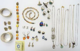 A group of mostly silver jewellery, comprising; seven rings, a reconstituted amber necklace,