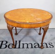 A Victorian style walnut oval centre table on tapering ball and claw supports,