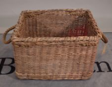 An early 20th century wicker basket with rope handles, 66cm wide x 44cm high.