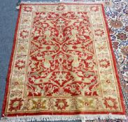A Turkish rug, the madder field with lily-head and floral vine design, cream palmette border,