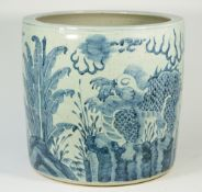 A large Chinese blue and white pottery jardiniere decorated with temple dogs against a landscape,