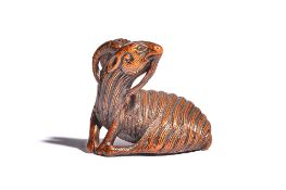 A Japanese wood netsuke of a recumbent goat, 19th century, carved with head turned across its back,