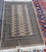 An Indian rug, the plain brown field with a lozenge medallion, grey spandrels, cross border,