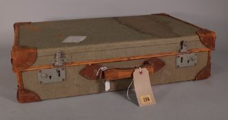 An early 20th century canvas and leather bound military suitcase, 63cm wide x 16cm high.