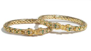 An Asian pair of gold and varicoloured gem set circular hinged bangles, each mounted with green,
