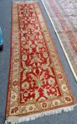A Turkish runner, the madder field with a palmette, acanthus leaf and flower vine design,