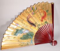 A large 20th century Japanese paper fan decorated with Koi carp, 75cm long x 118cm wide.