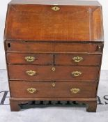 A George III oak bureau with welled interior over two short and two long drawers on bracket feet,
