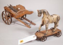 A 19th century painted wooden model of a horse, 20cm wide x 20cm high, a later associated cart,