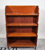 A Victorian mahogany and ebony inlaid four tier waterfall open bookcase on turned supports,