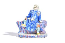 A rare Chinese famille-rose group, Qianlong, modelled as an open mouthed man seated on rockwork,