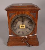 An early 20th century oak cased mantel clock with silvered dial and an eight day movement,