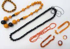 A coral bead necklace, two further bead necklaces, three reconstituted amber bracelets,