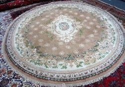 An Indian circular rug, the fawn field with floral ivory centre, floral border, 280cm diameter.