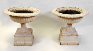 A pair of white painted cast iron campana shape terrace urns, 19th century,