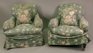 A pair of early 20th century upholstered deep seated armchairs,