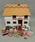 A child's modern dolls house, in the form of a 'thatched' two storey cottage,