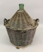 A large vintage green glass wine bottle, in two handled wicker casing, 70cm high.