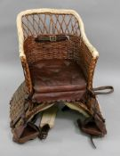 A child's Victorian wicker donkey seat, with leather cushion and straps, 35cm wide x 52cm high.