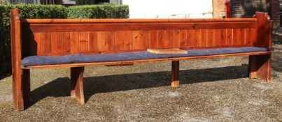 A long Victorian stained pine pew, 335cm