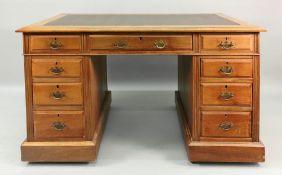 An Edwardian walnut kneehole desk, the i
