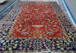 A Heriz carpet, Persian, the madder field with three central angular vases of flowers,