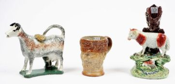 A Staffordshire pottery cow creamer, circa 1800, its coat sponged in brown, black and ochre,