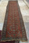 A North West Persian runner, the madder field with an allover herate design,