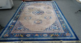 A Chinese carpet, the mushroom coloured field with a larger central leaf roundel,
