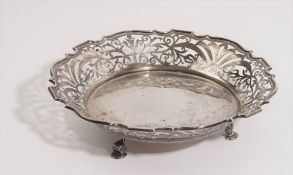 A silver bowl, of shaped circular form, having pierced decoration, raised on three feet,