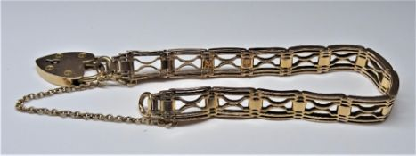 A gold curved bar link gate bracelet, on a gold heart shaped padlock clasp, detailed 15 CT,