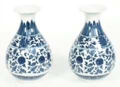 A pair of modern Chinese style porcelain vases, each foliate decorated against a waisted ground,