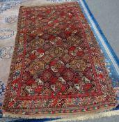 An Esari carpet, the dark brown field with three columns of seven and a half bold guls,